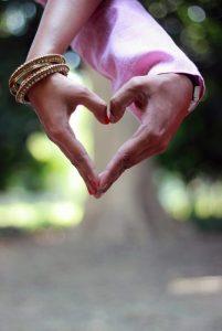 Zwei Hände, die sich liebevoll berühren und ein Herz bilden.