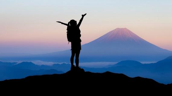 Power Posing. Eine Frau am Gipfel eines Berges mit erhobenen Armen, fühlt sich unschlagbar.