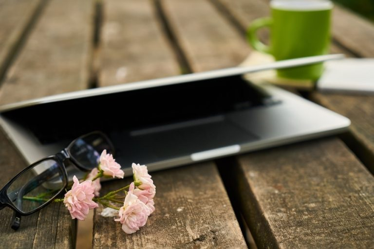 Laptop auf Holztisch mit Blume für Corporate Yoga Session.
