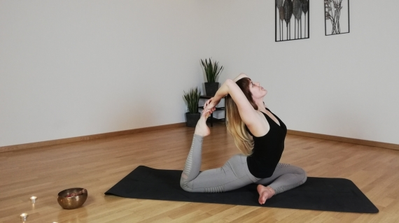 Yogatrainierin mianamaste im Yoga Kurs.