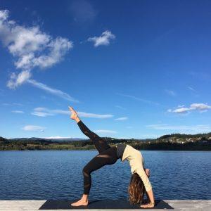 Yogatrainerin MiaNamaste im Rad am Steg am Längsee unter blauem Himmel.