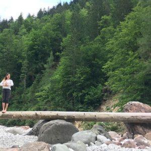 Yogatrainerin MiaNamaste auf einem liegenden Baumstamm in einem Flussbeet am Waldrand.